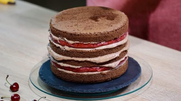 Příprava čokoládový dort s višněmi. Dort je prosáklý sladký sirup pro vlhkost.