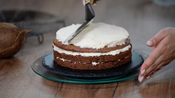 Zenske ruky šíří bílá šlehačka na čokoládový piškotový dort