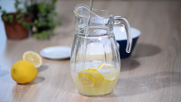 Gießen Sie Wasser in einen Krug mit Zitronen. Glas Sekt Soda trinken Limonade mit Eis Wasser und Kalk Zitronenscheibe auf weißem Hintergrund.