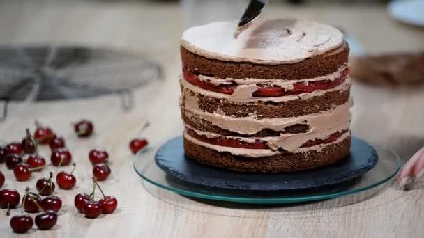 Krok za krokem Příprava černé značkové dortu. Cukrář pokrývá dort se smetanou.