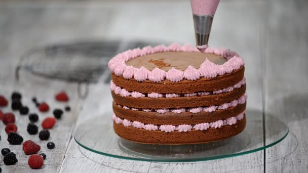 Készül, így a csokoládé torta bogyók. Womans kézzel díszíteni a tortát.