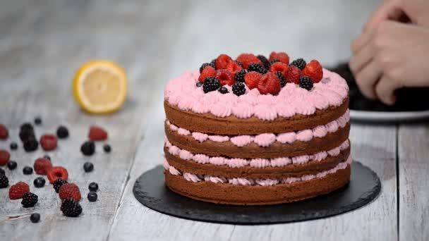 Séf díszíteni a tortát vad bogyók.