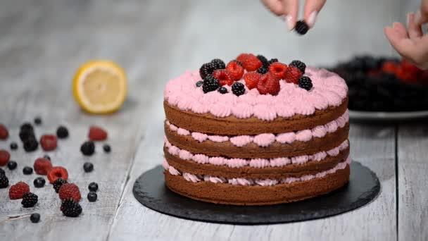 cukrář zdobí dort s ovocem