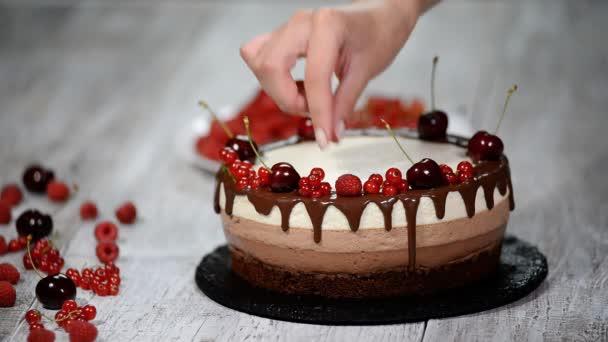 Trojitá Čokoládový mousse dort zdobený čerstvé bobule.