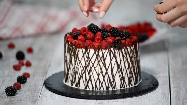 Díszíteni a tortát a bogyós gyümölcsök és csokoládé. Házi sütemény.