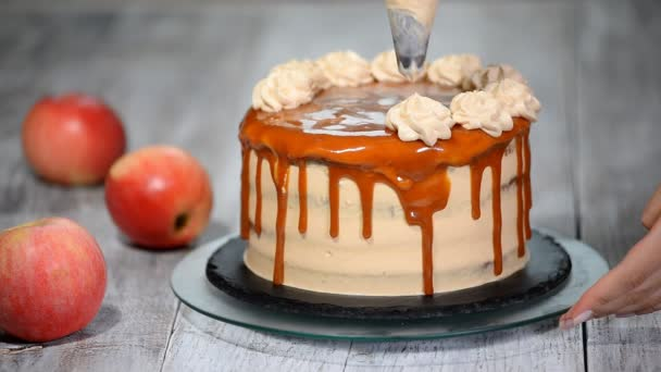 Close-up of woman decorating cake. Making Caramel Apple Cake.
