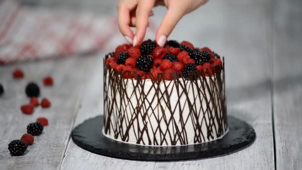 cukrář zdobí dort s ovocem.