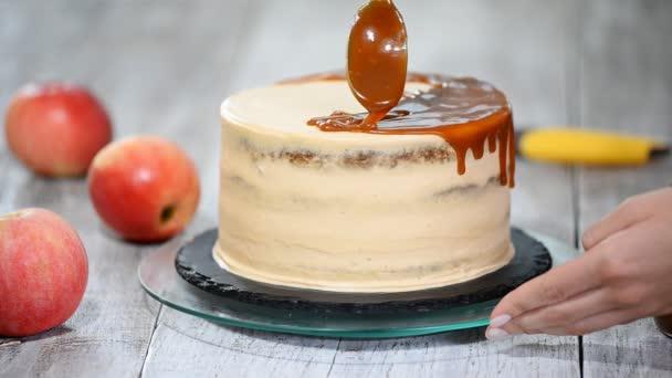 Mladá žena použití Karamelová omáčka na lahodné domácí koláče u stolu. Lahodný dort s jablky a šlehačkou krémovou náplní.