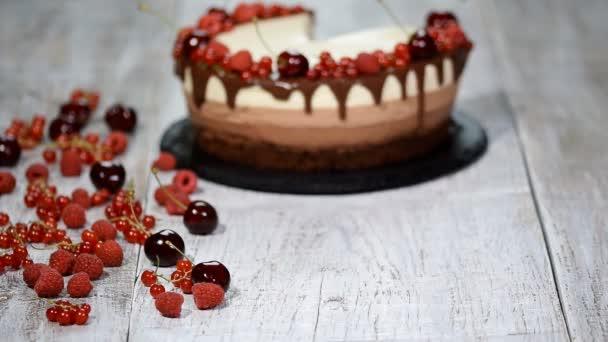 Kus výborné tři čokoládové mousse dort zdobený čerstvým berry.