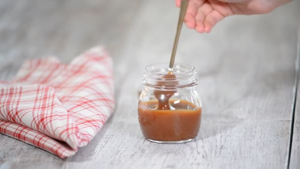 Lžíce s chutné karamelovou omáčkou nad sklenici na stole