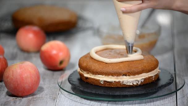 K nepoznání ženské pečivo kuchař mačkání krém na dort chutná vrstva v kuchyni.