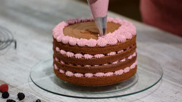 Lépésről lépésre. Baker egy színes vajkrém fagyosan csokoládé torta összeszerelése.
