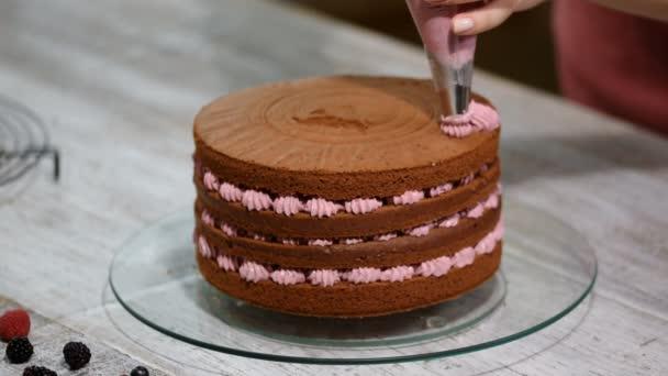 Krok za krokem. Baker, kompletace čokoládový dort s polevou barevné buttercream.