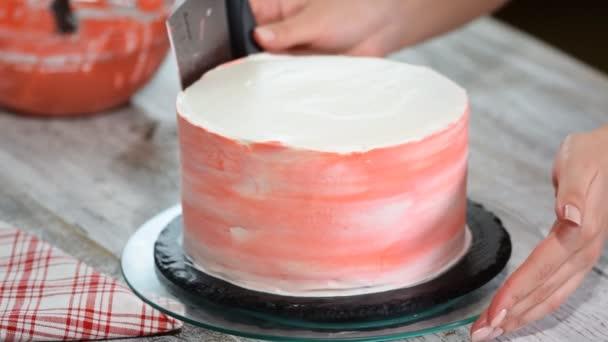 Detailní záběr ženy v pekárně zdobení dort s polevou.