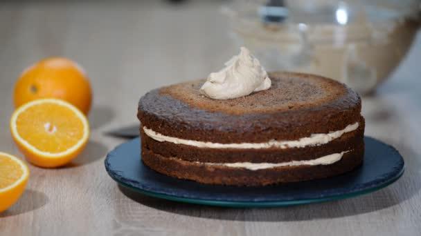 Close up of chef put cake layer on cream. Cooking layered cake. Making layered pie. Chocolate cake layers