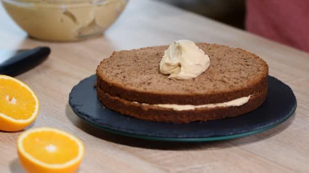 Zblízka se šéfkuchaře nasadil dortíkovou vrstvu krému. Vaření vrstvený dort. Výroba vrstvený koláč. Čokoládový dort vrstev.