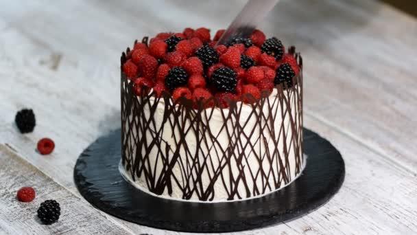 Moderní rustikální vertikální řezání roll vysoký dort s berry.