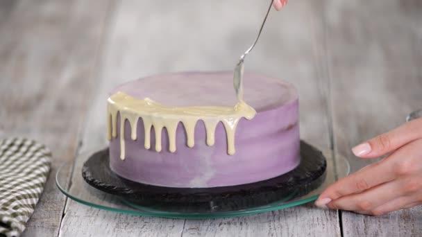 Příprava prázdninového koláče. Ta holka nalije tekutou bílou čokoládu.