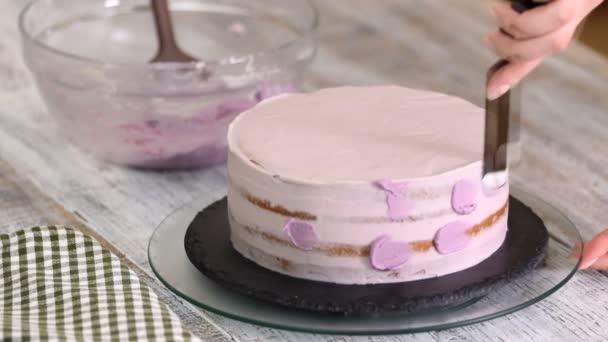 Proces zdobení dort s fialovým krém krytem. Cukrář se rovná sušenka krémem pomocí špachtle těsto.