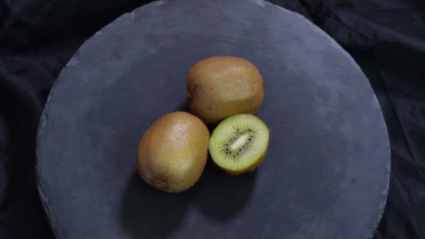 Rotating kiwi fruit on black background. Top view.