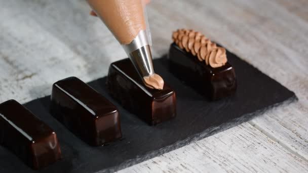 Čokoládové koláče se smetanou. Francouzský moučový dort pokrytý čokoládovou glazou.