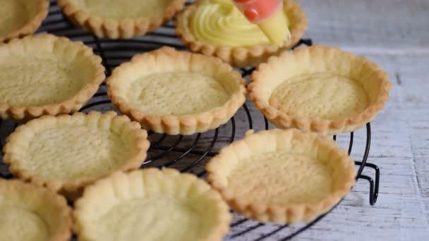 Girl fills tartlets with custard. Pastry. Sweet tartlets dessert.