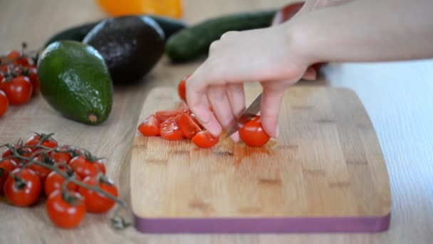 Woman is cutting cherry tomatoes for the salad on the wood table.