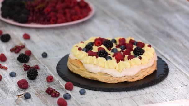 Šéfkuchař dělá dort s pudinkovou a rybídovou bobulí, maliny, ostružiny, borůvky. Vynikající dezert.