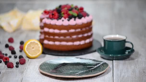 Finom csokoládé torta bogyók és a csésze tea a táblázat közelről.