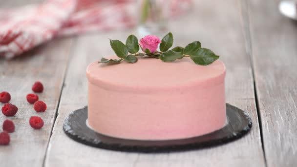 Cukrárník zdobí růžový koláč s růžemi.