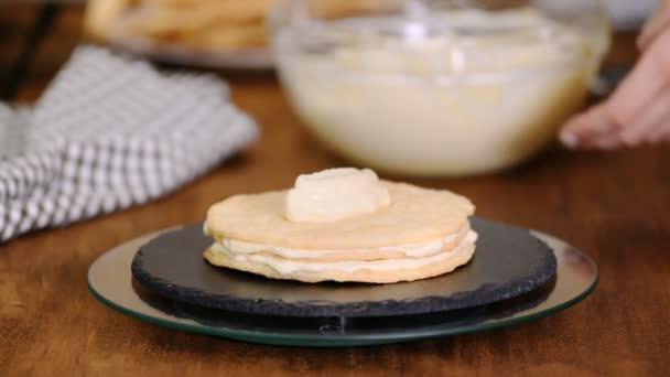 Vytváření vrstev Napoleonových koláčů doma: šlehačku na pečené pečivo.
