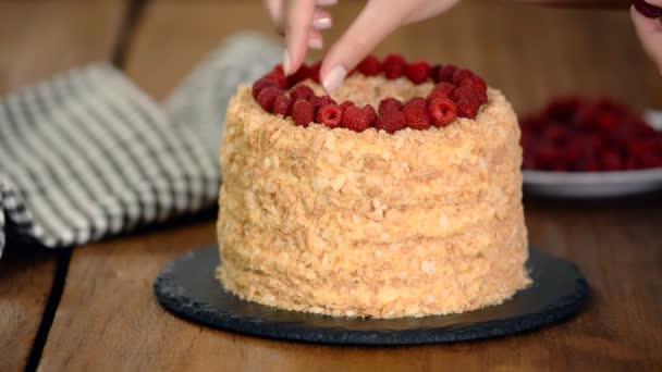 Cukrár zdobí Napoleonův vrstvený dort s čerstvým malinovou.