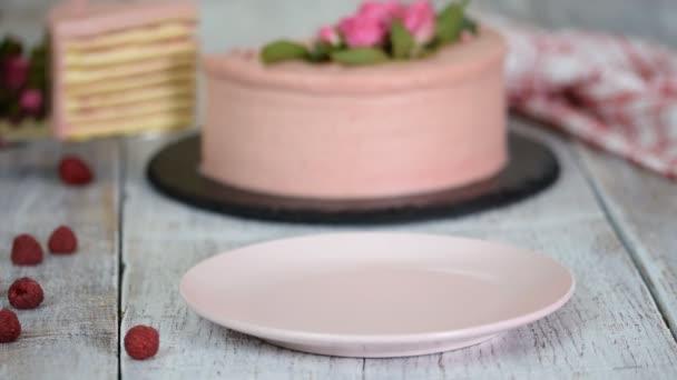 Kousek lahodného vrstveného dortu s malinovou omáčkou.