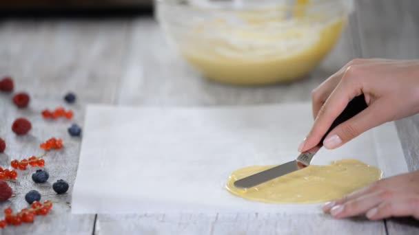 Záběry cukrárníka, který dělá základnu pro dort nebo dortík.
