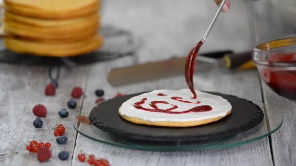 Cukrárna rozmazává smetanu po vrstvách dortu. Proces pečení dortu s bobulovou nádivkou.