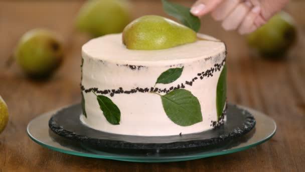 A lány cukrász friss körtével díszíti a csokitortát. A házi sütemény, a sütemények koncepciója.