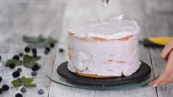 Cukrárna v kuchyni dělá houbový dort s jahodovou smetanou. Koncept domácího pečiva, koláče na vaření. Řady