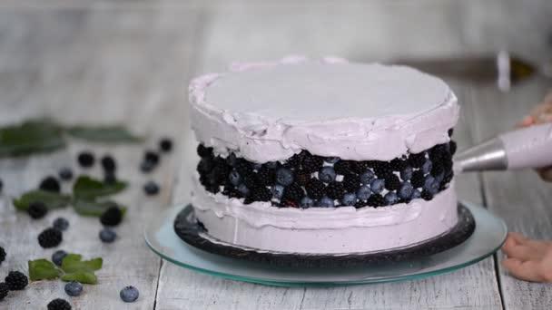 Cukrárna v kuchyni dělá houbový dort s jahodovou smetanou. Koncept domácího pečiva, koláče na vaření. Řady.
