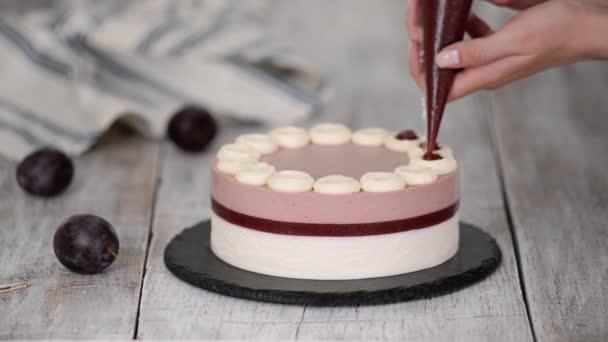 Sütőipari szakács díszített egy finom szilva mousse torta lekvárral.