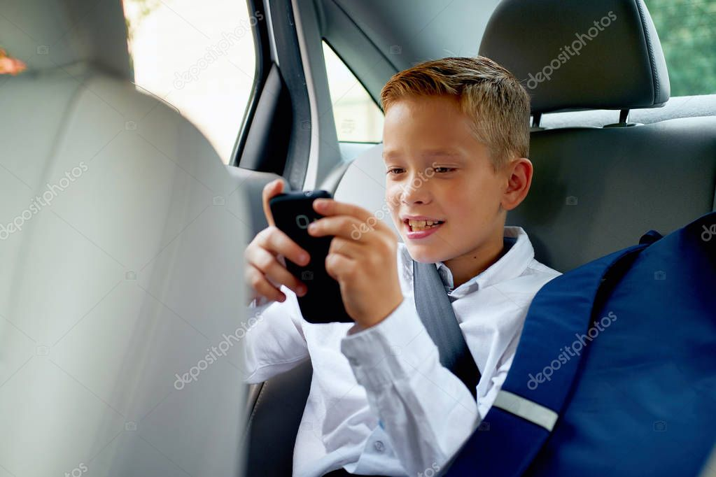 Child sitting in car and playing games on his cell phone