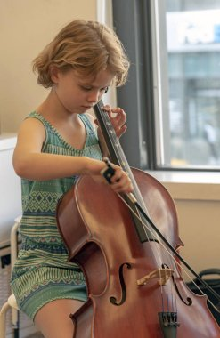 Young music student playing a cello