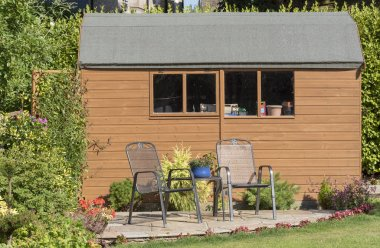 A Dutch style wooden garden shed with patio and two chairs