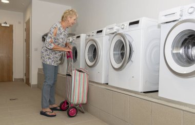 Elderly woman with her dirty washing trolley checking the washing machine in a laundry room