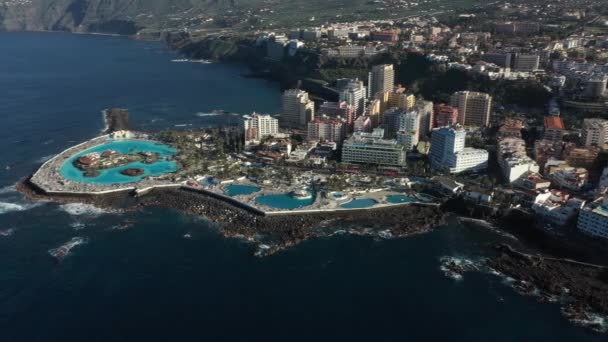upper view round swimming pools near hotels washed by waves