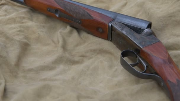 Vintage hunting rifle and binoculars lie on a khaki tent.