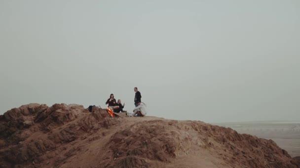 Skupina lidí relaxuje na vrcholu hory při západu slunce, sedí blízko táboráku, užívají si svůj čas - přátelství, mládež, full hd