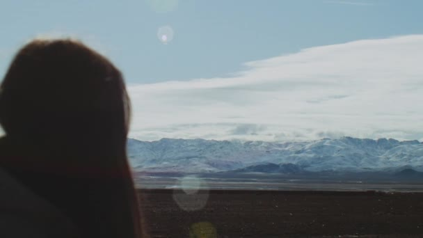 Woman standing and watching to the top of the Atlas Mountains, with panoramic snowy peaks and cloudy sky, sun bunnies to the camera, Morocco, full hd