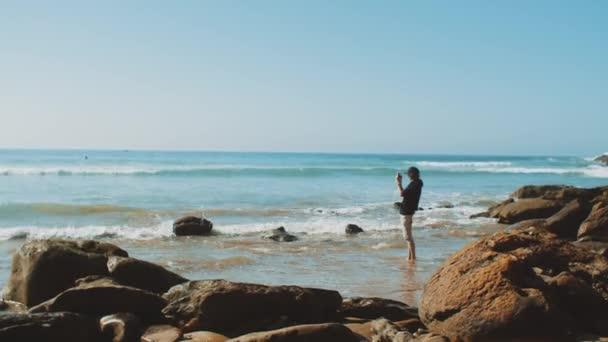 Mann fotografiert mit Smartphone am Strand, das Meer im Hintergrund, steinige Küste, Tourist in Marokko, voll hd