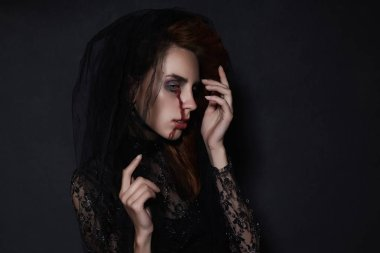woman in black veil with a bloody face make-up.halloween costume.black widow