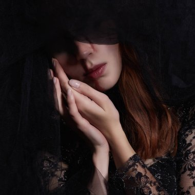 sad woman in black veil with a bloody face make-up.halloween costume.black widow